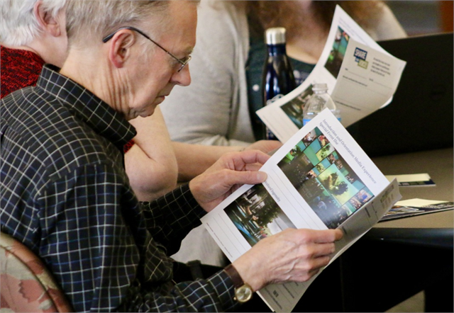 "Mike Thompson examines a packet of concept exhibit design renderings for a new state history museum during the Wisconsin Historical Society's ""Share Your Voice"" listening session in Kenosha."
