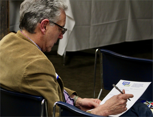 UW-Milwaukee history professor Joe Rodriguez writes his comments on a packet of concept exhibit design renderings during the Wisconsin Historical Society's listening session for the Latinx community of Milwaukee on May 15, 2019.