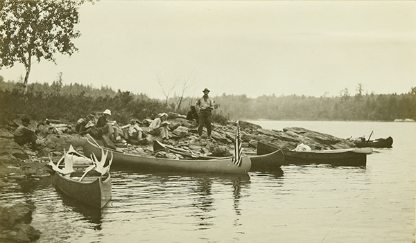 The Gang stopping at Sand Point for a lunch break. The canoes are at the edge of the shoreline, while everyone is sitting on the ground eating.