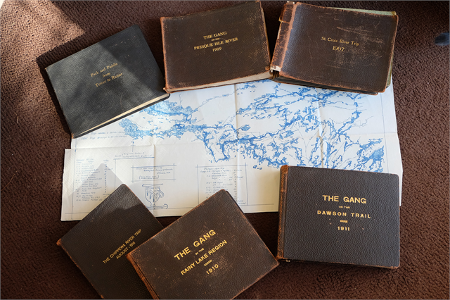 Photography journals created by Howard Greene, placed on a map of the boundary lakes.
