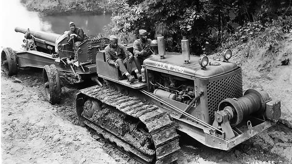 Three African American field artillery soldiers (from Battery F of the 349th Field Artillery, Fort Sill, Oklahoma) crossing a creek on a TD-18 diesel crawler tractor and 155 mm gun. The commanding officer of the 349th was Colonel A.L.P. Sands.