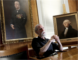 Photograph of Barry Bauman seated at a table in front of portraits by Sargent and Sully