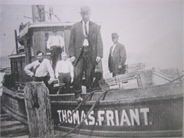 A historic, black and white photo of five men standing on a fish tug boat