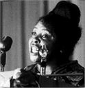 African American female political figure and civil rights activist Fannie Lou Hamer speaking into microphones.