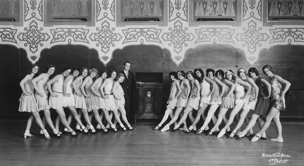 Leo Kehl in a line with 21 female dance students. The young women are posed in a kickline position, and most are wearing skirts, socks and tap or ballroom shoes.