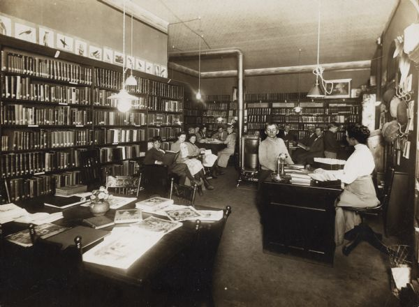 Interior view of the Brodhead Public Library, occupied by several people.