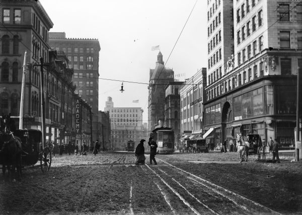 A muddy street in Milwaukee with a streetcar, horse-drawn carts and pedestrians.