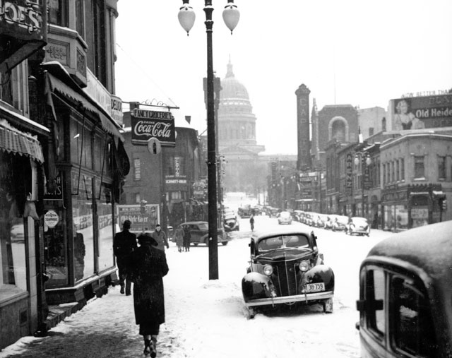 A snowy street scene with a distant glimpse of the capitol.