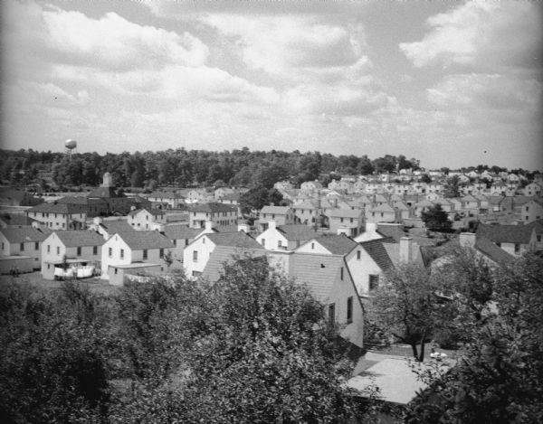 Elevated view over trees of village. A water tower is visible on a hill with trees in the background.