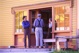 Three men talk on the porch of the general store.
