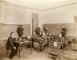 Classroom view of male and female students as they read and practice math. A teacher looks on from the head of the class.