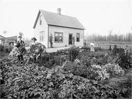 Julius Koehler family in their garden in front of their newly built frame home.