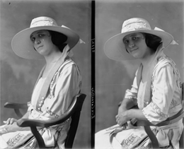 A girl sitting in a chair, shown from the waist up in two views, one reflective and one smiling. She is wearing a broad-brimmed hat and a white dress.