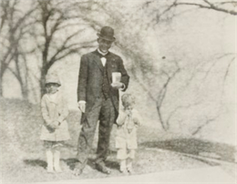 Snapshot of Booker T. Washington and two small children.