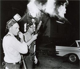 Freedom House in flames after Milwaukee Police fired tear gas into the building. Two armed officers stand in front of the burning building. Both officers have gas masks on their heads. WHI 48147.