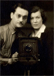 A studio portrait of Harold and Vivian Hone posing with a camera.