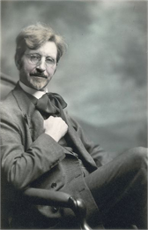 A seated self-portrait of the photographer, Ephraim Burt Trimpey. He wears eyeglasses, and a suit with vest and floppy cravat.