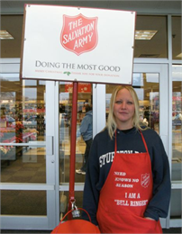 "A female Salvation Army bell ringer poses outside Shopko. Apron reads; ""need knows no season - I am a bell ringer."""