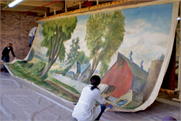Conservators working on one 28 foot panel of the mural on an oversized easel.