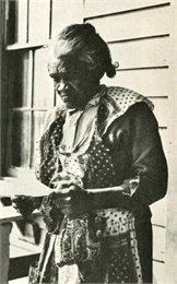 An elderly black woman reading a pamphlet on her porch.