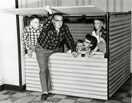 A middle-aged man stepping into small metal crate shelter while holding up a hinged upper door. His wife and four kids are inside the shelter.