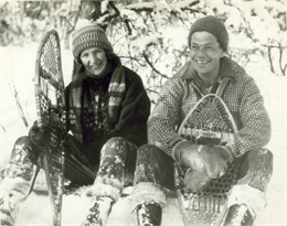 A couple sitting outdoors in the snow holding snowshoes.