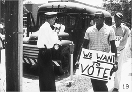 Two black men hold protest signs walking down a sidewalk past a white police officer who is holding a speaker megaphone. In the background, a police vehicle is parked on the curb.