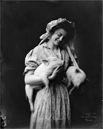Young woman poses in a dress and bonnet in a studio. She is holding two young pigs.