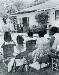 A group of African American women sitting outside, listening to an African American speaker.