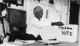 "Two female poll workers sit behind a table near a box with the words: ""Freedom Vote"" written on it."