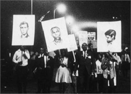 A nighttime rally on a boardwalk. Three people carry signs with portraits of missing project workers.