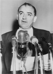 Joseph McCarthy speaking in front of multiple microphones about the clash between himself and President Eisenhower.