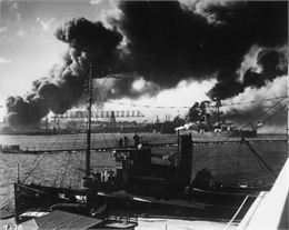 A tug boat in the foreground and a battleship sit in Pearl Harbor with smoke rising.