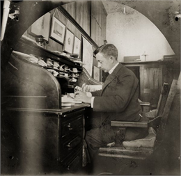 Middle-aged Thwaites in a suit viewing papers at his desk.