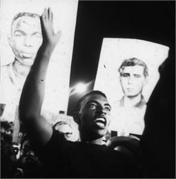 A young man at a nighttime rally in support of the MFDP. Behind him people carry placards with portraits of James Earl Chaney and Andrew Goodman, two of the three civil rights volunteers murdered during Freedom Summer of 1964.