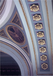 Detailed photo of the ceiling in the Capitol that includes Includes paintings of an eagle and decorative plasterwork.
