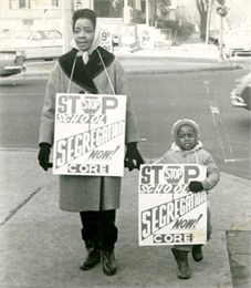 A woman and small child are standing on a sidewalk with 'Stop School Segregation' signs.