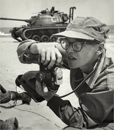 Dickey Chapelle, holding her camera while framing in a shot. There is a tank in the background.