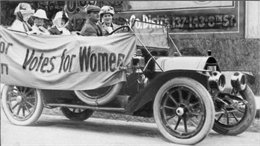 "An early car carrying four women and one man, has a banner on it saying ""Votes for Women""."