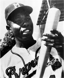 Head and shoulders portrait of Henry Louis 'Hank' Aaron with a Milwaukee Braves uniform on holding a baseball bat.
