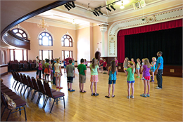 Interior of Heyde Center for the Arts. Group of school children standing in a circle in the former high school gym learning about theater.