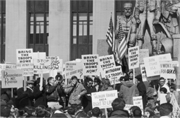 Crowd holding picket signs at an anti-Vietnam War rally in Pioneer Park in Minneapolis.