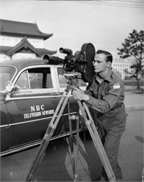 A U.N. war correspondent is shown filming with a news camera next to an NBC Television Newsreel vehicle.