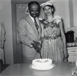 Lewis Arms and his new wife LuRay pose in their wedding clothes, cutting the wedding cake.