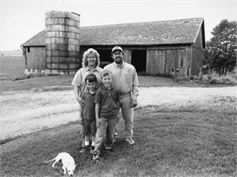 Brian and Lisa Adelmeyer and sons standing in front of barn.