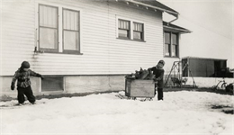 Young Richard and Ralph Quinney hauling firewood on a sled through the snow past the farmhouse.