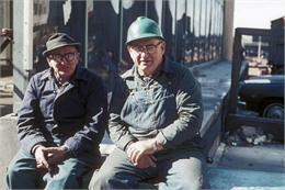 Two construction workers take a break at the side of the building of the World Trade Center.