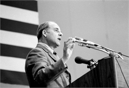 Gaylord Nelson speaking at a podium on Earth Day.