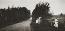 Ada Bass leaning against a fence, next to Everetta Bass as a young girl, along a dirt road. Another unidentified woman is also leaning against a fence.