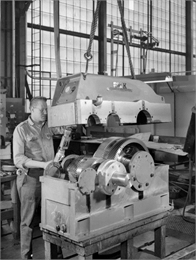 "Ron Kudlewski, a Falk employee, attends to the test stand for large motors in the High Speed Department. This motor was later purchased and used by the Louis Allis Company. Falk caption reads, ""5000 HP unit 1800/3600 rpm."""